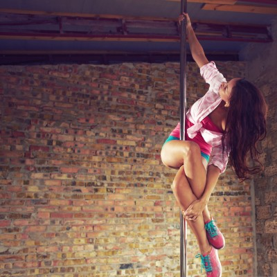 Young pole dancer woman wearing colorful sports wear trains on grunge interior with brick walls, right side align, square composition